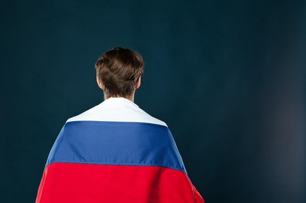 Mens die de vlag van rusland op zwarte muur houdt