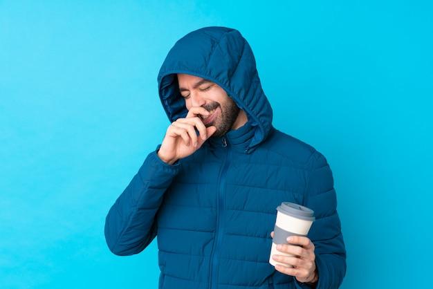 Mens die de winterjasje draagt en een meeneemkoffie over geïsoleerd blauw houdt die veel glimlacht