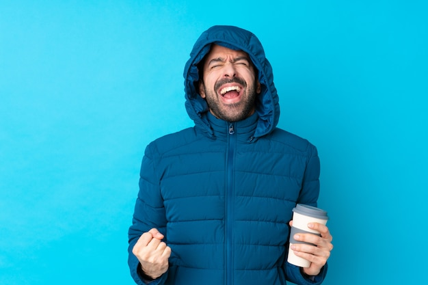 Mens die de winterjasje draagt en een meeneemkoffie over geïsoleerde blauwe muur houdt die aan de voorzijde met wijd open mond schreeuwt