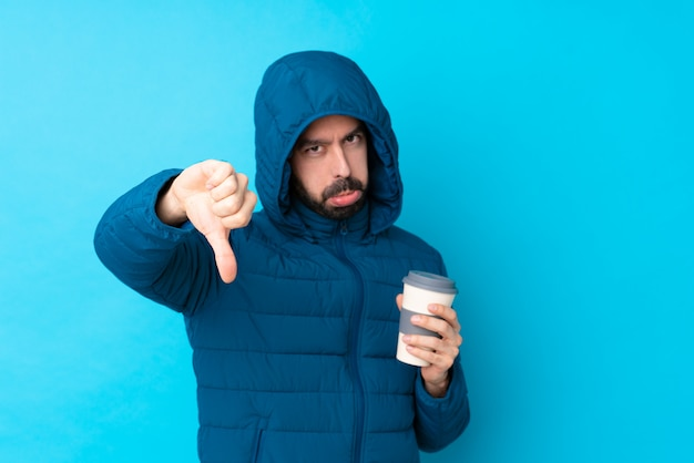 Mens die de winterjasje draagt en een meeneemkoffie over geïsoleerde blauwe muur houdt die duim met negatieve uitdrukking toont