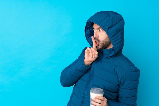Mens die de winterjasje draagt en een meeneemkoffie over geïsoleerde blauwe muur houdt die een teken van stiltegebaar toont