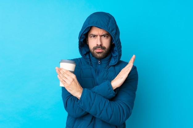 Mens die de winterjasje draagt en een meeneemkoffie over geïsoleerde blauwe muur houdt die geen gebaar maakt