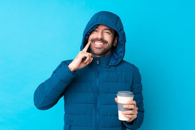 Mens die de winterjasje draagt en een meeneemkoffie over geïsoleerde blauwe muur houdt die met een gelukkige en prettige uitdrukking glimlacht