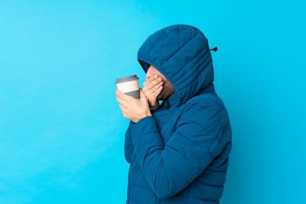 Mens die de winterjasje draagt en een meeneemkoffie over geïsoleerde blauwe muur houdt die mond behandelt en aan de kant kijkt