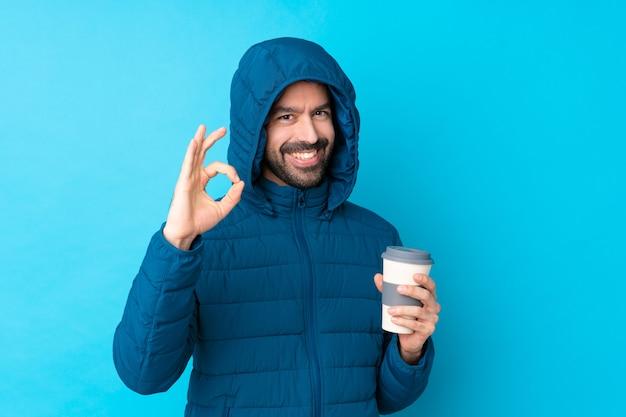 Mens die de winterjasje draagt en een meeneemkoffie over geïsoleerde blauwe muur houdt die ok teken met vingers toont