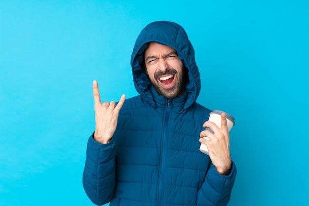 Mens die de winterjasje draagt en een meeneemkoffie over geïsoleerde blauwe muur houdt die rotsgebaar maakt