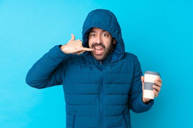 Mens die de winterjasje draagt en een meeneemkoffie over geïsoleerde blauwe muur houdt die telefoongebaar en het twijfelen maakt