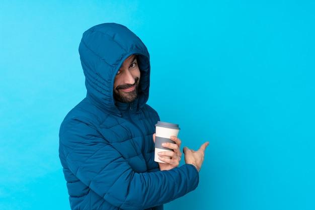 Mens die de winterjasje draagt en een meeneemkoffie over geïsoleerde blauwe muur houdt die terug richt
