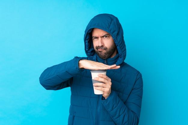 Mens die de winterjasje draagt en een meeneemkoffie over geïsoleerde blauwe muur houdt die tijd opmaken gebaar