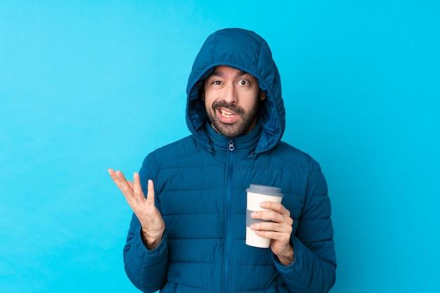 Mens die de winterjasje draagt en een meeneemkoffie over geïsoleerde blauwe muur houdt die twijfelgebaar maakt