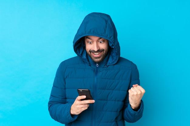 Mens die de winterjasje draagt en een meeneemkoffie over geïsoleerde blauwe muur houdt verrast en een bericht verzendt