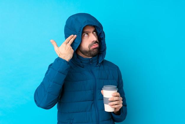 Mens die de winterjasje draagt en een meeneemkoffie over geïsoleerde blauwe muur met problemen houdt die zelfmoordgebaar maken