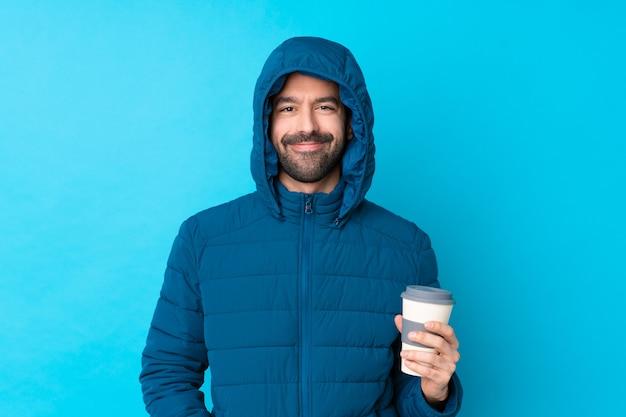 Mens die de winterjasje draagt en een meeneemkoffie over het geïsoleerde blauwe muur lachen houdt