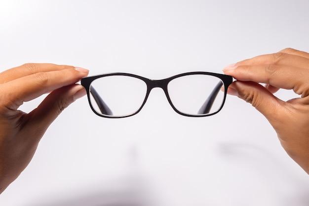Mens die de zwarte bril van oogglazen met glanzend zwart geïsoleerd kader houdt
