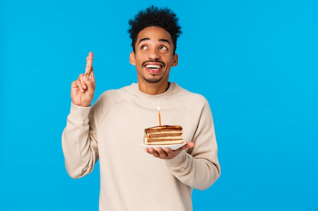 Mens die denkt welke wens idee heeft. afrikaanse amerikaanse creatieve gelukkige en opgewekte kerel die vinger eureka gebaar opheffen glimlachen, houdend b-dag cake met kaars, het nadenken, status blauw