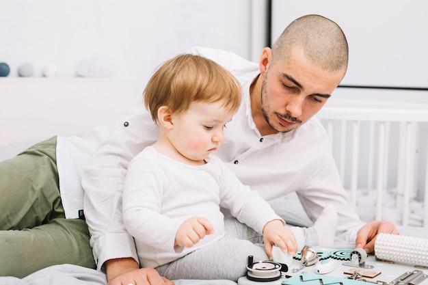 Mens die dichtbij weinig baby met stuk speelgoed het zitten op bed dichtbij voederbak liggen