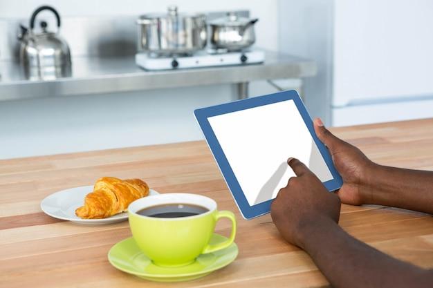 Mens die digitale tablet gebruiken terwijl het hebben van ontbijt in keuken