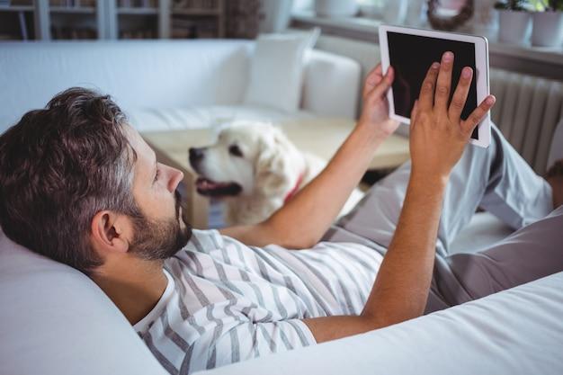 Mens die digitale tablet in woonkamer gebruikt