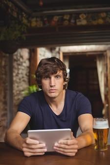 Mens die digitale tablet met bierglas gebruiken op lijst