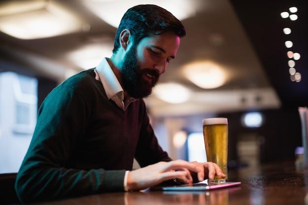 Mens die digitale tablet met glas bier op teller gebruiken