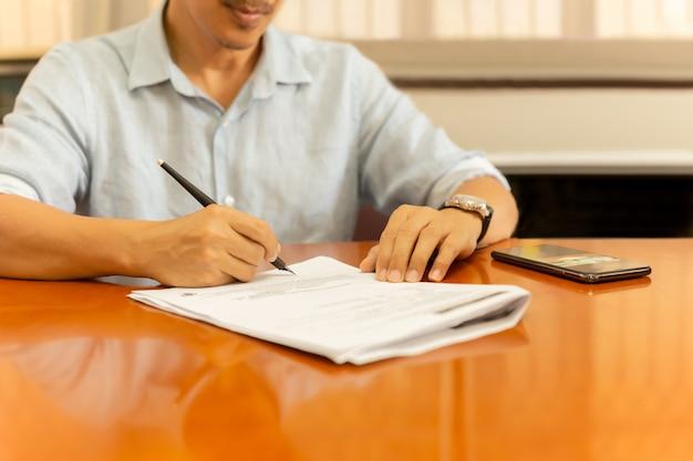 Mens die documenten met ganzepen op houten bureau ondertekenen.