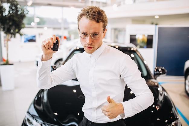 Mens die duimen voor een auto in een autotoonzaal tonen