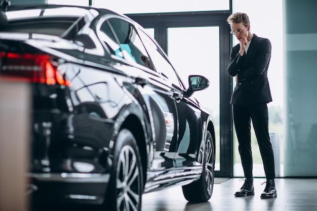 Mens die een auto bekijkt en aan een aankoop denkt