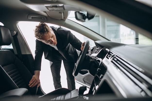 Mens die een auto in een autotoonzaal bekijkt