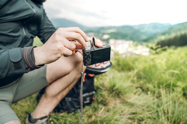 Mens die een batterij op een digitale camera in de aard introduceert