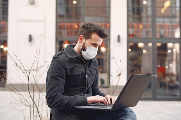 Mens die een beschermende maskerzitting in de stad met laptop draagt