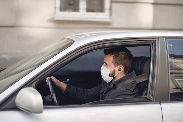 Mens die een beschermende maskerzitting in een auto draagt