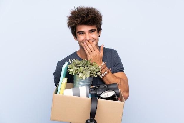 Mens die een beweging maakt terwijl het oppakken van een doos vol dingen met verrassende gelaatsuitdrukking