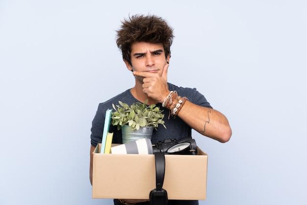 Mens die een beweging maakt terwijl hij een doos vol dingen oppakt die een idee denken