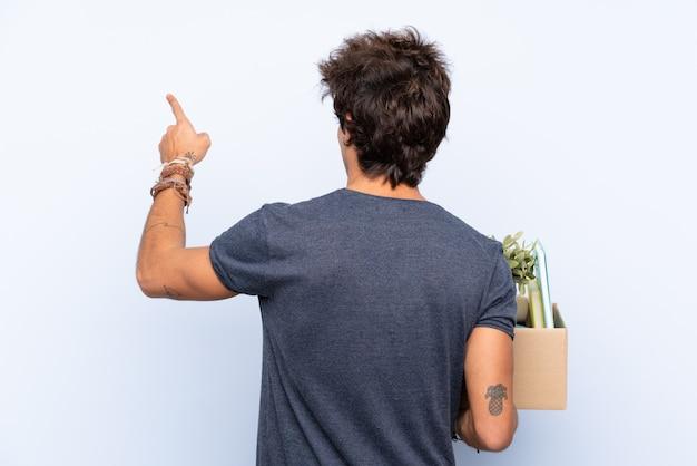 Mens die een beweging maakt terwijl hij een doos vol dingen oppakt die met de wijsvinger terug wijzen