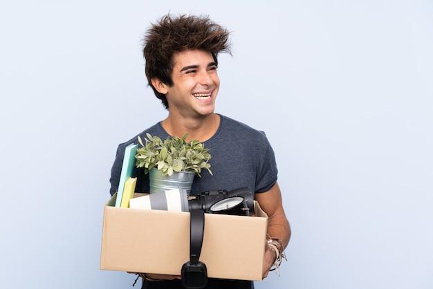 Mens die een beweging maakt terwijl hij een doos vol dingen oppakt die naar de kant kijken