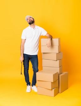 Mens die een beweging maakt terwijl hij een doos vol dingen oppakt
