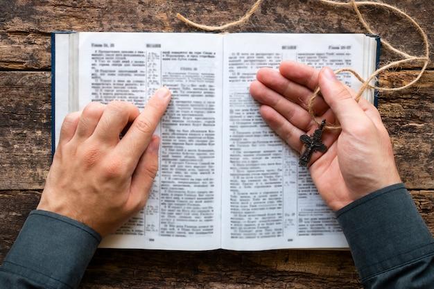 Mens die een bijbel leest en een kruis houdt