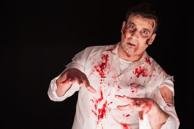 Mens die een bloedig zombiekostuum over zwarte achtergrond voor halloween draagt. creatieve make-up.