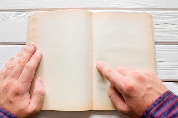 Mens die een boek op een witte houten achtergrond leest