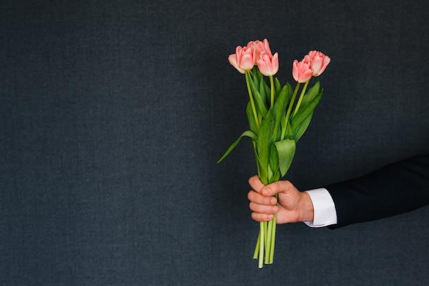 Mens die een boeket van roze tulpen geeft