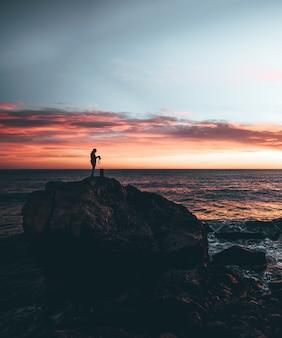 Mens die een camera in de bovenkant van een rots met een zonsondergang houdt