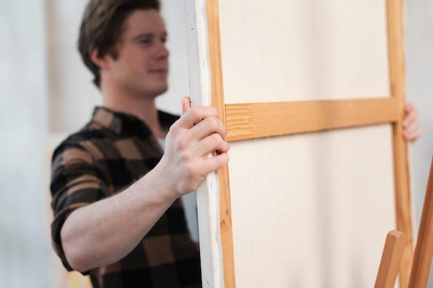 Mens die een canvas op een schildersezelclose-up zet