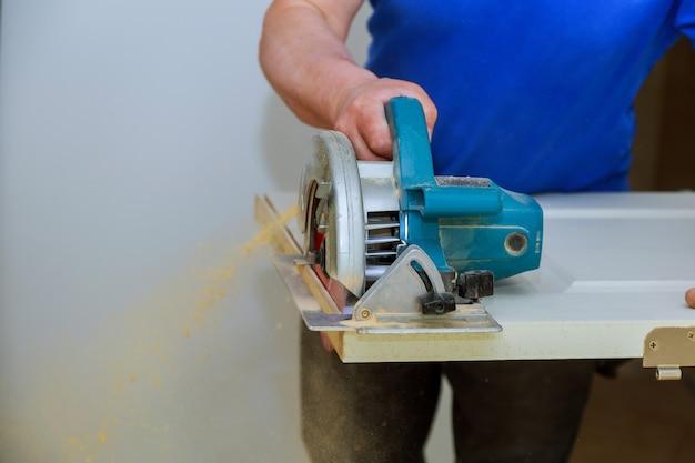 Mens die een cirkelzaag voor het snijden van houten deurbouw en huisvernieuwing gebruikt