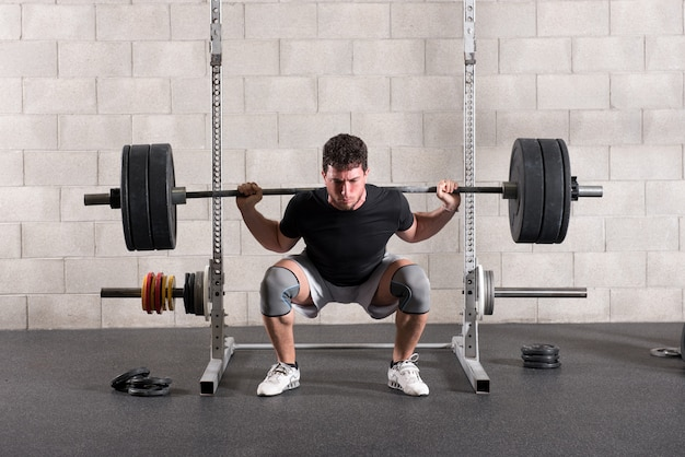Mens die een crossfit achter hurkende oefening doet