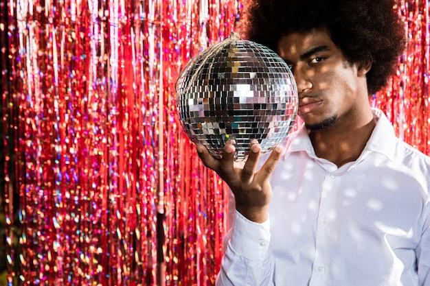 Mens die een discobal en exemplaar ruimteachtergrond houdt