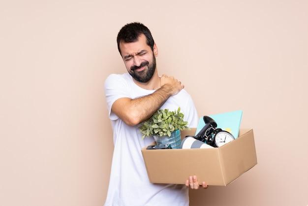 Mens die een doos houdt en zich in nieuw huis beweegt dat aan pijn in schouder lijdt omdat het een inspanning heeft geleverd