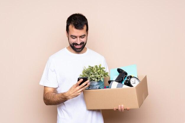 Mens die een doos houdt en zich in nieuw huis beweegt dat een bericht met mobiel verzendt