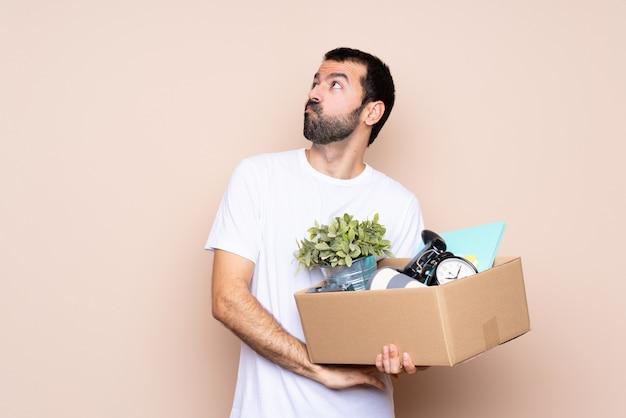 Mens die een doos houdt en zich in nieuw huis beweegt dat twijfelgebaar maakt terwijl het opheffen van de schouders