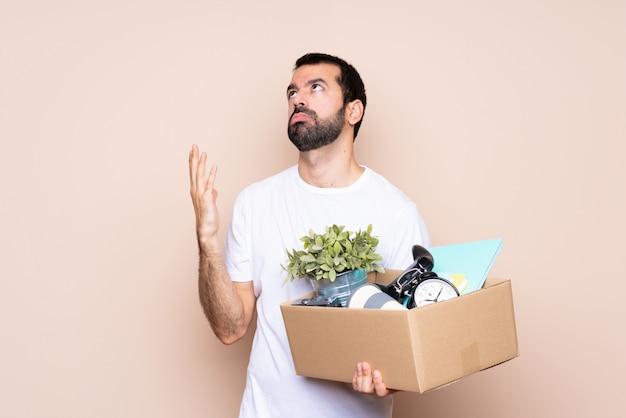 Mens die een doos houdt en zich in nieuw huis beweegt gefrustreerd door een slechte situatie