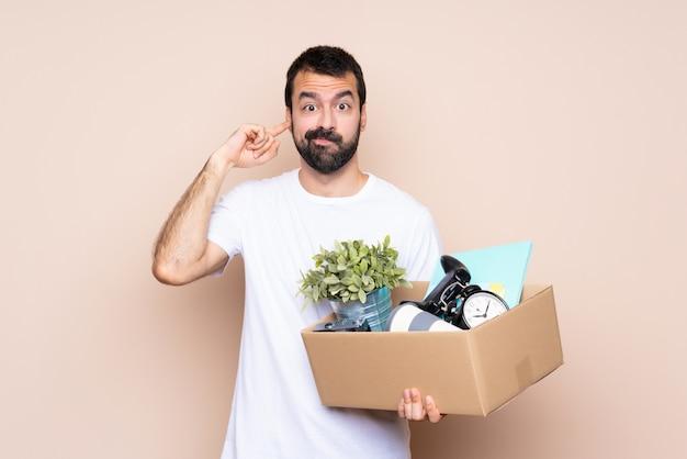 Mens die een doos houdt en zich in nieuw huis over geïsoleerde gefrustreerde muur beweegt en oren behandelt
